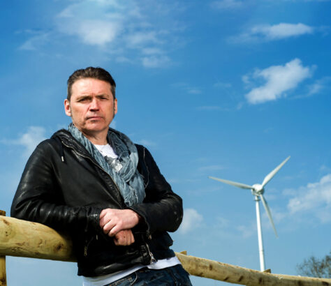 Dalve Vince Leaning on a fence with ecotricity wind turbine behind him