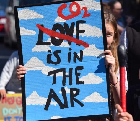 Sign held up with CO2 is in the air (Love crossed out)