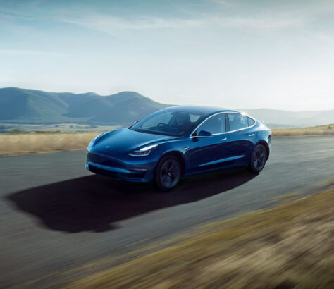 Tesla Model 3 driving on a road through plains with mountain back drop