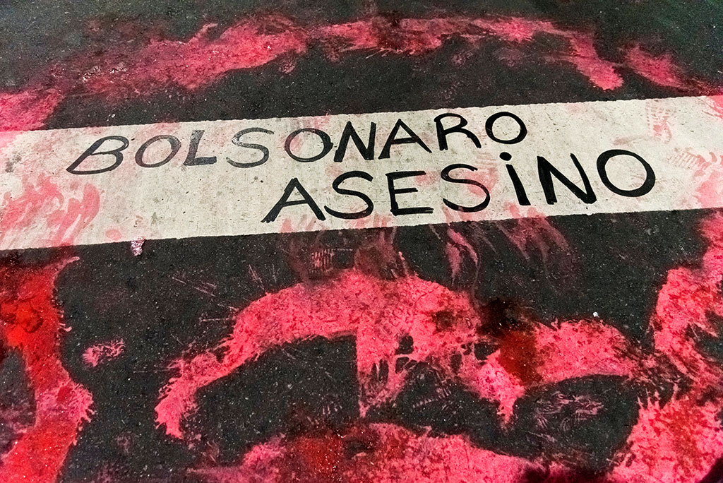 Text painted in the street: Bolsonaro, murderer. Protest for the protection of the Amazon and against Brazilian environmental policies