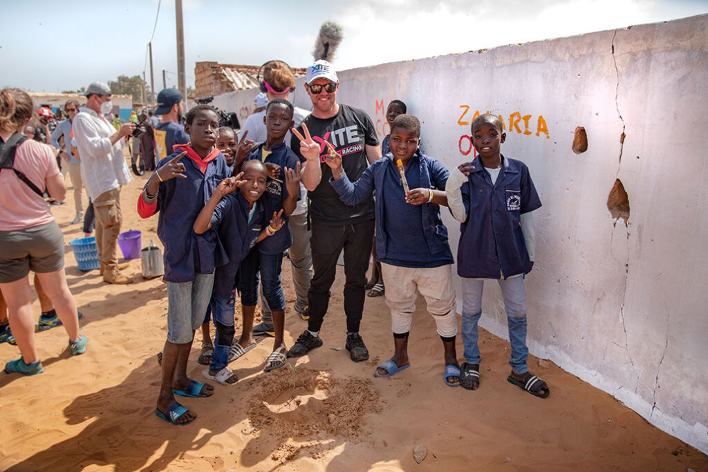 Oliver Bennett, driver of Hispano Suiza race team, with local students painting a mural during the Ocean X Prix, Senegal