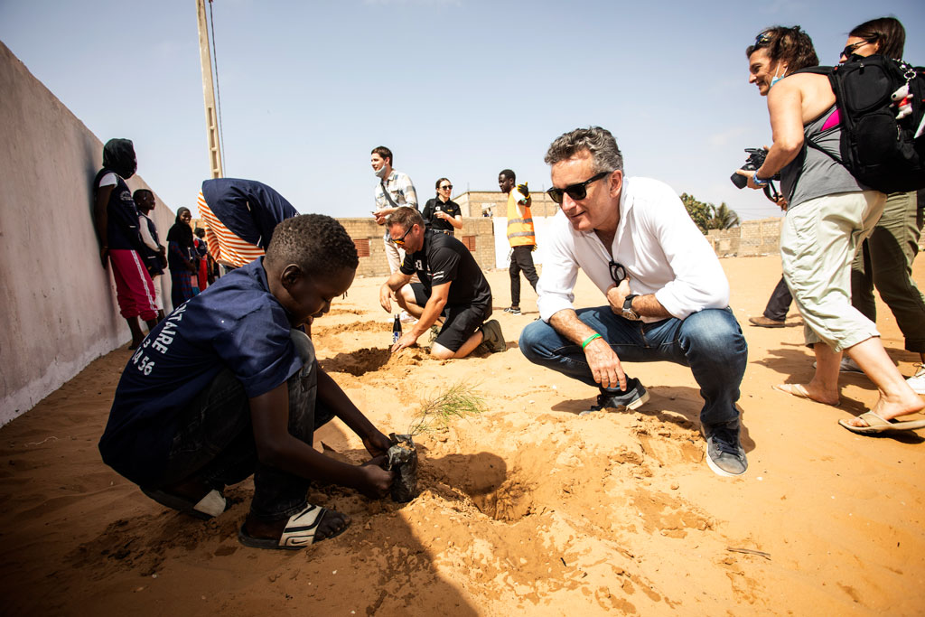 Pupil of local school with Alejandro Agag, CEO Extreme E planting Filao saplings which help protect the soil from coastal erosion