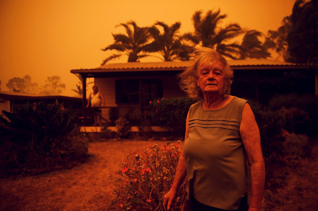 Nancy Allen and Brian Allen stand outside the house as high winds push smoke and ash from the Currowan Fire towards Nowra, New South Wales, Australia